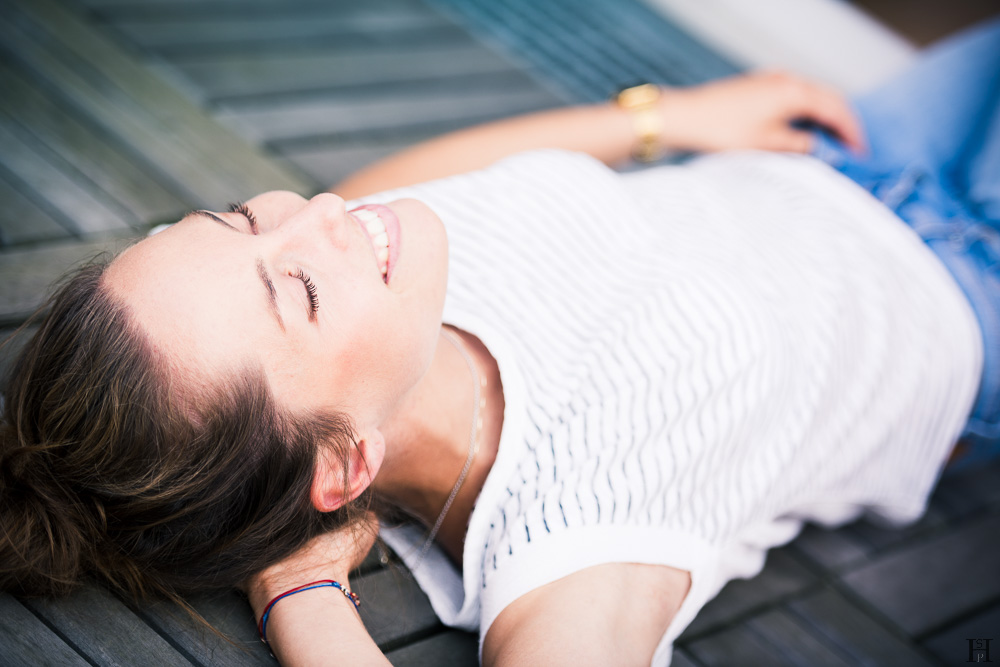 Young beautiful girl lying on a wooden floor smiling