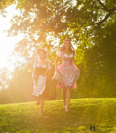 Girls in traditional German/Austrian dresses (called Dirndl) running down a hill with the sun setting behind them.