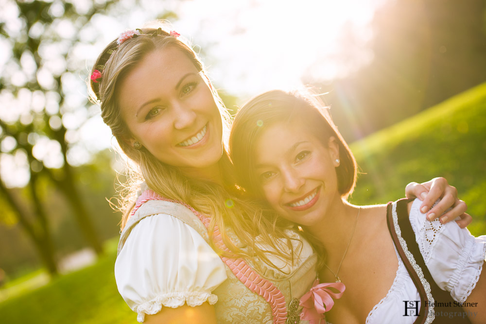 Portrait of two girls in traditional German/Austrian dresses (called Dirndl) with the sun setting behind them.